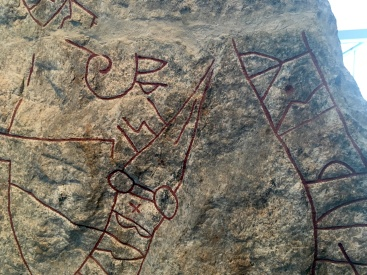A close up of a viking memorial stone, with red runes carved into the rock.
