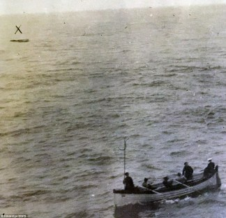 5 people in a lifeboat in the lower right-hand corner, looking off into the distance towards the upper left-hand corner, where another, distant lifeboat appears as a thin line, and is marked with an X that's been drawn over the photo. The sea occupies the bulk of the photo and the horizon is visible only faintly at the very top.